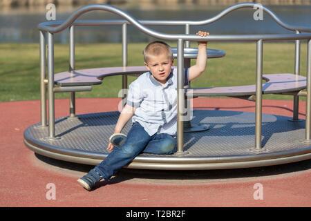 Petit garçon sur une aire de jeux. Enfant jouant à l'extérieur en été. Les enfants jouent sur la cour de l'école. Happy kid à la maternelle ou à la garderie. Les enfants s'amuser à