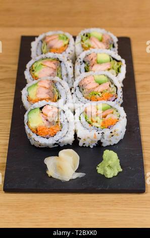 Le saumon, l'avocat et carotte sushi roll servi sur une plaque en ardoise avec du gingembre et wasabi, selective focus et les détails Banque D'Images