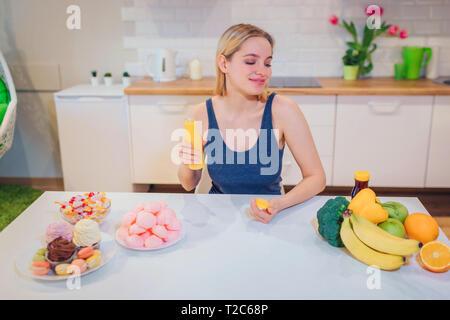 Young smiling woman détient l'eau detox tout en choisissant entre les aliments sains et malsains dans la cuisine. Choix difficile entre fruits frais Banque D'Images