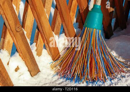 Un balai en plastique avec des soies multicolores de la pile se trouve dans la neige. Le concept de nettoyage de la zone de neige en hiver.Close-up de l'obj Banque D'Images