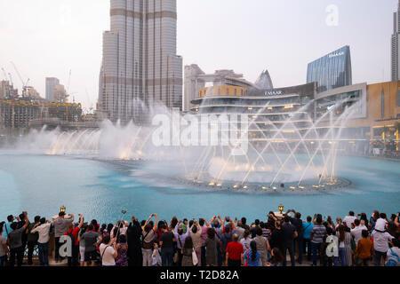 Les gens qui regardent les jets synchronisés de l'eau afficher sur le lac en face de la gratte-ciel Burj Khalifa à Dubaï, Émirats Arabes Unis Banque D'Images