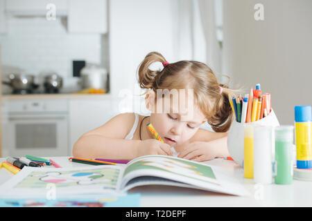 Jolie petite fille sérieuse avec deux queues est le dessin dans un livre à colorier avec stylo-feutre à la maison. Shot de près. Arrière-plan flou. Banque D'Images