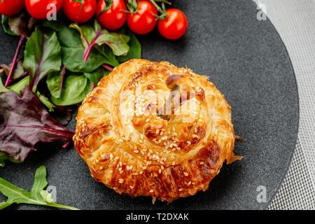 Pilons de poulet dans la pâte cuite au four avec des pommes de terre, tomates, oignons et épices avec une salade de tomates et de salade verte. Banque D'Images