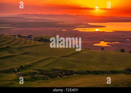 Soleil au-dessus d'un champ d'éoliennes eoliennes et une vallée avec un lac et d'une herbe de pâturage des moutons sur une colline Banque D'Images