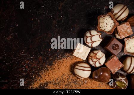 Arrière-plan de chocolats. Le chocolat. Assortiment de chocolats fins en blanc, noir, et de chocolat au lait Banque D'Images