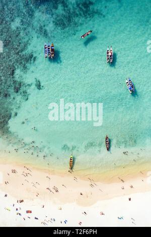 Vue de dessus, vue aérienne d'une belle plage tropicale avec sable blanc et eau claire turquoise, longue queue des bateaux et des gens de soleil.