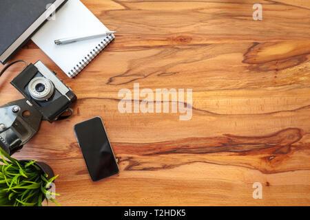 Feuilles de papier, l'appareil photo rétro et smartphone sur table. Banque D'Images