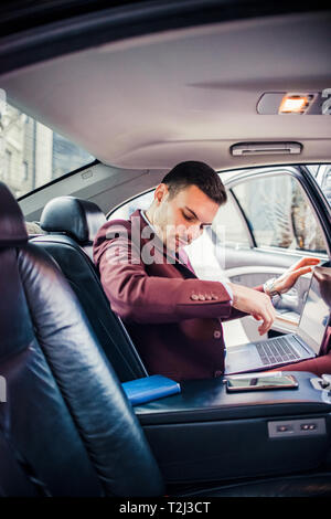 Handsome businessman avec lap top assis sur les sièges arrière d'une limousine Banque D'Images