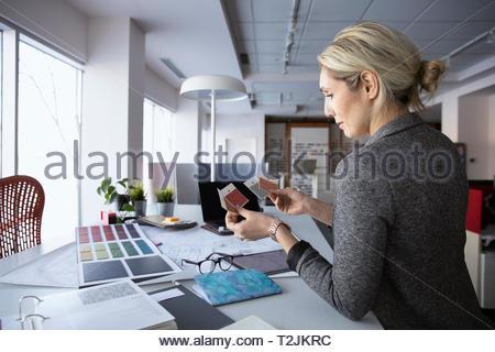 Femme d'intérieur de l'examen de nuanciers dans design studio Banque D'Images