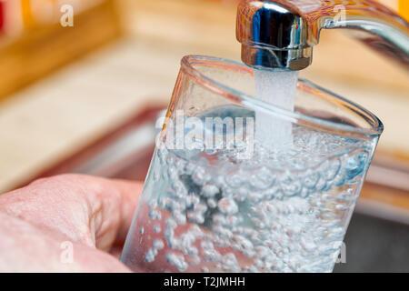 Libre tourné d'un homme de servir un verre d'eau douce dans un robinet de cuisine Banque D'Images