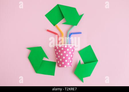 Eco concept avec symbole de recyclage et à usage unique tasse de papier avec des pailles en plastique sur fond rose pastel un minimum de concept créatif. Banque D'Images
