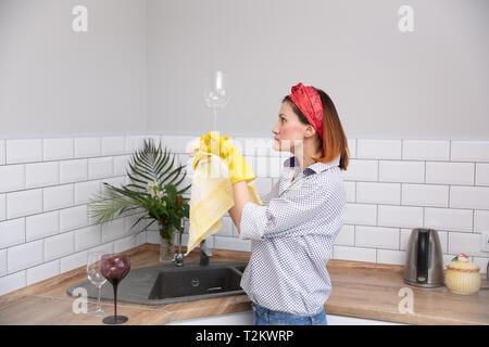 De nettoyage ou de femme verre ruges dans la cuisine. de ménage faire le nettoyage de printemps