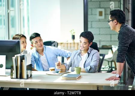 Quatre jeunes dirigeants d'Asie qui travaillent ensemble à discuter du plan d'office. Banque D'Images