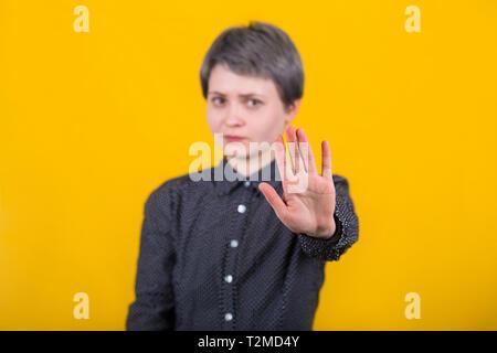Close up portrait of woman, sérieux montrant arrêter geste avec sa main, faisant des gestes interdiction, pas de signe, looking at camera isolated over yell