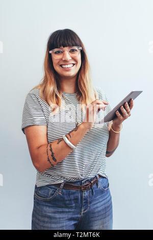 Close up of a smiling businesswoman standing avec un tablet pc dans la main. Portrait d'un entrepreneur gaies travaille sur un tablet pc in office. Banque D'Images