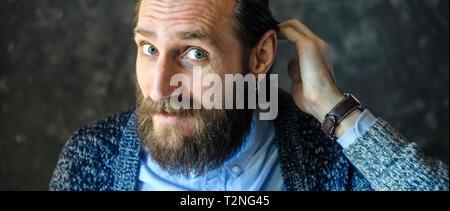 L'homme confus avec une barbe se redresse nerveusement ses cheveux. Concept d'émotion dans l'embarras