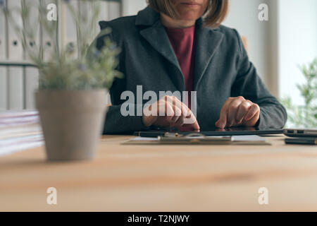 Businesswoman using tablet in office, la technologie contemporaine moderne cuisine dans des opérations commerciales Banque D'Images