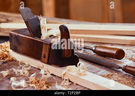 Avion en bois Vintage sur une planche de bois entourés de copeaux de lissage de la surface avec une râpe, fichier et du bois sur un établi