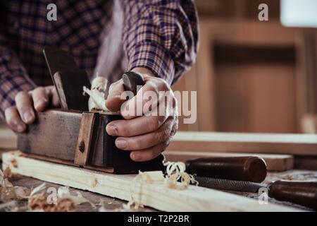 Menuisier charpentier ou fabricants d'une planche de bois le lissage de la surface dans une vue en gros plan sur ses mains et l'outil sur un établi