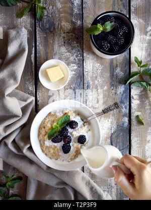 Petit-déjeuner d'été avec du porridge, de la crème et des mûres à village maison d'été