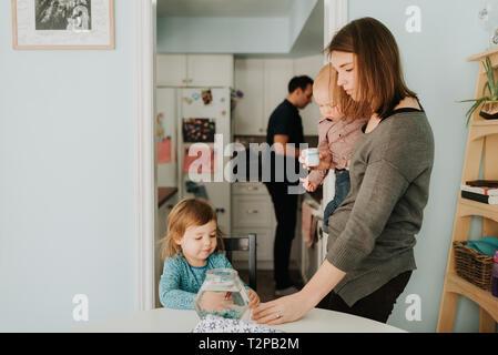 Female toddler à table avec la mère et le petit frère Banque D'Images