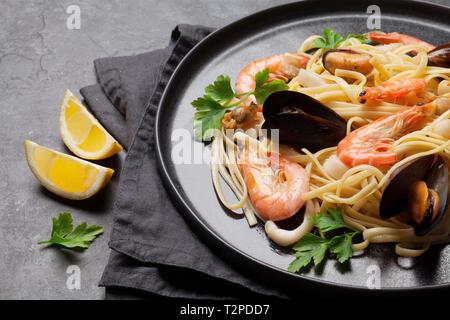 Pâtes aux fruits de mer Spaghetti aux palourdes et langoustines sur table en pierre Banque D'Images