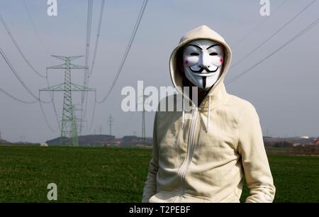 Velvary, RÉPUBLIQUE TCHÈQUE – 27 février 2019 : l'homme porte le masque Vendetta comme pirate informatique sur le champ vert avec pylon électrique