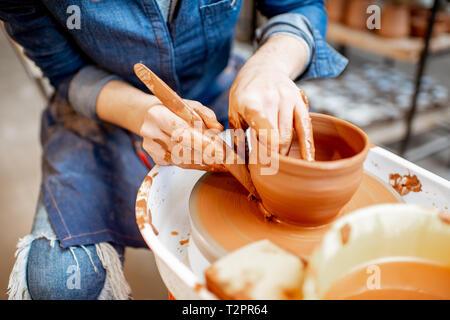 Woman making clay pot formant une forme avec l'outil spécial sur la roue de poterie, close-up view