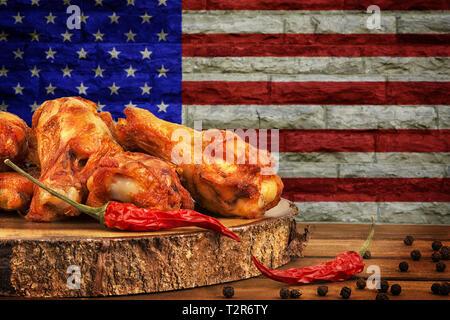 Ailes de poulet avec du piment, du sel et de poivre sur la table en bois. L'image du drapeau USA en arrière-plan. Banque D'Images