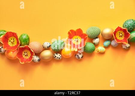 Mise à plat de Pâques sur fond de papier orange. Ou ligne frontière courbe faite de fleurs tulipes et oeufs de Pâques Banque D'Images