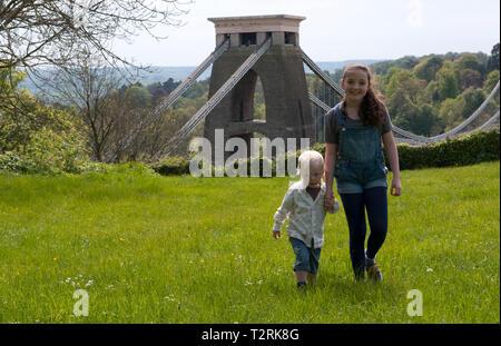 Jeune fille tenant les mains avec un petit garçon marchant vers l'appareil photo Banque D'Images