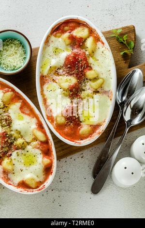 Boulettes de pommes de terre italienne gnocchi alla sorrentina de fromage mozzarella, cuit au four avec une sauce tomate et fines herbes. Servi avec du parmesan et des épices. Banque D'Images