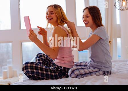 L'heure joyeuse. Deux belles soeurs transmission bénéficiant d'achats en ligne et le faire pour chaque d'autres coiffures Banque D'Images