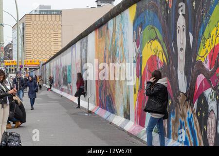 Les touristes en marche, prise de photos et posant devant des murales à l'East Side Gallery, section du mur de Berlin à Berlin, Allemagne. Banque D'Images