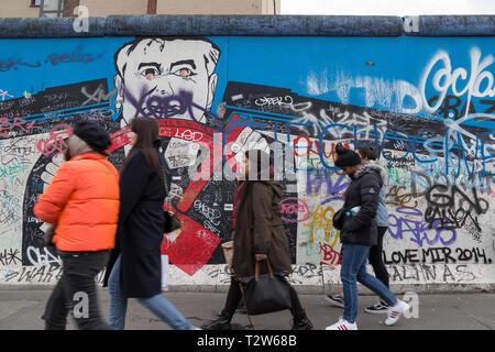 Les touristes à pied par murale, graffiti, tags et écrits à la East Side Gallery, la section du mur de Berlin à Berlin, Allemagne. Banque D'Images
