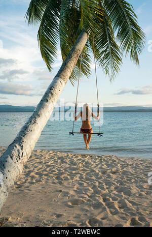 Vue arrière de la femme dans une plage swing attaché à un palmier dans les îles San Blas. Destination de voyage, de vie / Maison de concept. Panama, Oct 2018 Banque D'Images