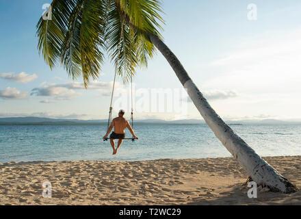 Vue arrière de l'homme dans une plage swing attaché à un palmier dans les îles San Blas. Destination de voyage, de vie / Maison de concept. Panama, Oct 2018 Banque D'Images