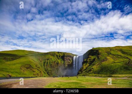 Les touristes à la Skogafoss, l'une des plus grandes cascades islandaise sur la rivière Skoga, attraction touristique populaire dans le sud de l'Islande, Scandinavie Banque D'Images