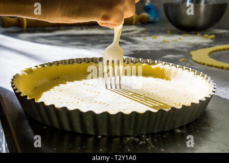 À l'aide d'une fourchette pour créer des trous dans la pâte d'un gâteau dans un laboratoire Banque D'Images