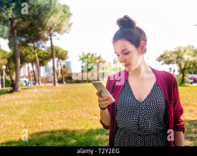 Young woman checking cell phone outdoors Banque D'Images
