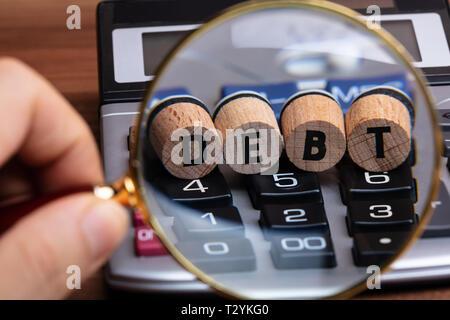 La main de l'examen de mot sur la dette par Liège Loupe sur Calculatrice Banque D'Images