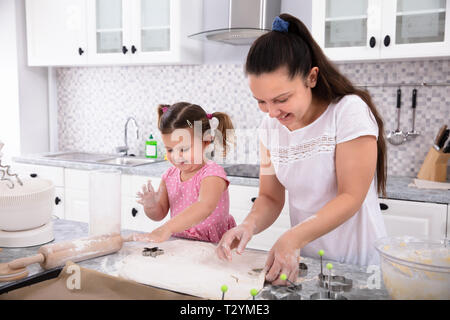 Happy Mother and Daughter Making Cookies avec Moules à cuisine Banque D'Images