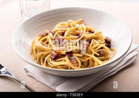 Spaghetti alla Carbanara à partir de la Lazio, Italie avec oeuf, fromage pecorino romano, généralement, de poivre et de guanciale ou porc servi dans un bol à table Banque D'Images