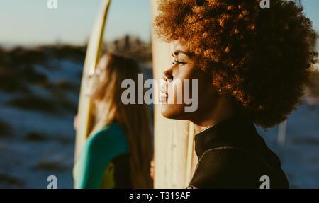 Close up of young African woman holding a surfboard et regardant le coucher du soleil avec son ami debout à l'arrière. Deux femmes sur la plage de surfers