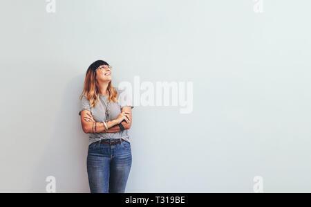 Femme en jeans et tshirt debout contre un mur à l'écart. Comité permanent de l'entrepreneur avec les mains pliées. Banque D'Images