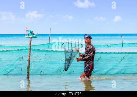 Pêcheur vietnamien à l'aide d'un filet et les filets de pêche au large de la côte de Bai Dai Tay plage dans le golfe de Thaïlande, l'île de Phu Quoc, Vietnam, Asie. Banque D'Images