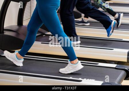 Close up jambes de personnes sur des tapis roulants modernes dans une salle de sport. Vue sur la partie inférieure Banque D'Images