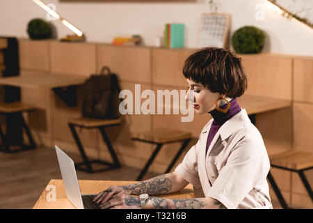 Attractive businesswoman using laptop while sitting at table in cafeteria Banque D'Images