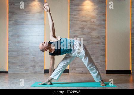 Sports man looking up avec bras soulevé faisant du yoga sur tapis bleu en salle de sport. Banque D'Images