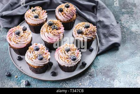 De délicieux petits gâteaux avec crème de myrtilles, de bleuets frais et l'écrou sprinkel. Banque D'Images